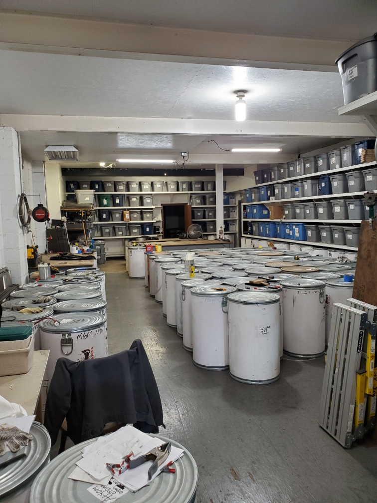 multiple large white drums and grey rubbermaid storage containers